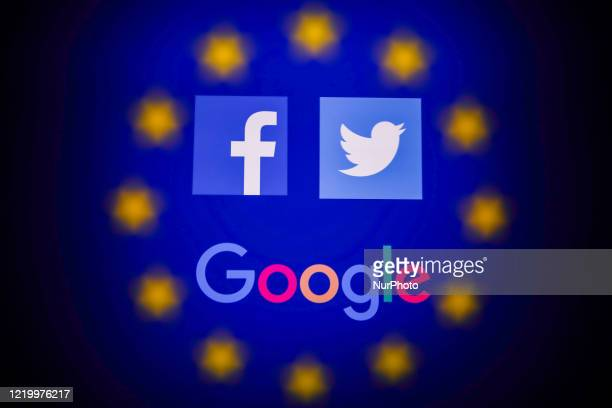 Facebook, Twitter and Google logos displayed on a phone screen and European Union flag displayed on a screen in the background are seen in this...