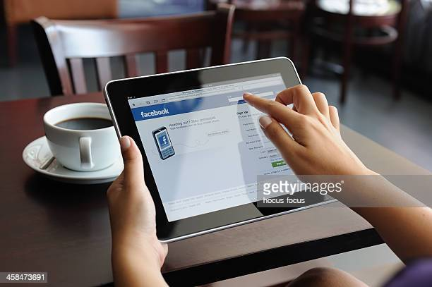 facebook web page on ipad apple digital tablet - log on stock photos and pictures
