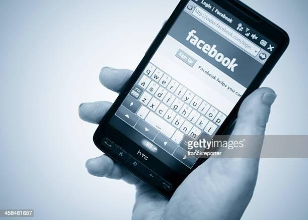 facebook-seiten auf smarthphone - ganzkörper freisteller editorial stock-fotos und bilder