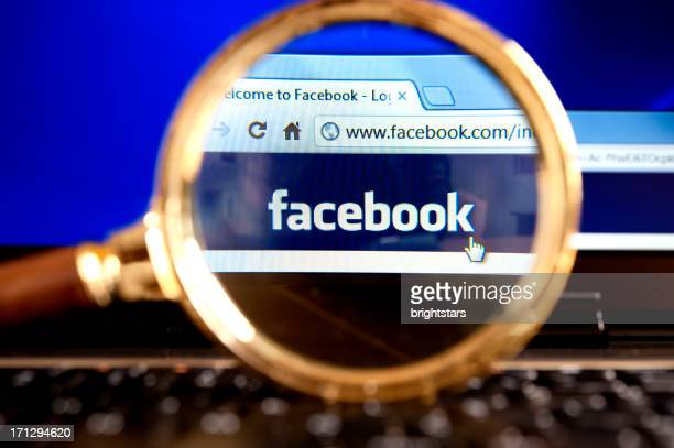 facebook website through a magnifying glass - magnifying glass icon stock photos and pictures