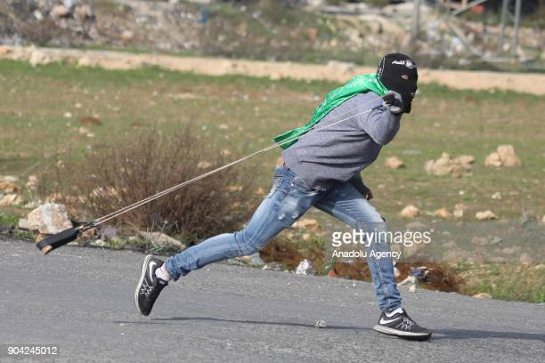 A facecovered protester attempts to throws a rock with a slingshot in response to Israeli security forces' intervention in a protest against US...
