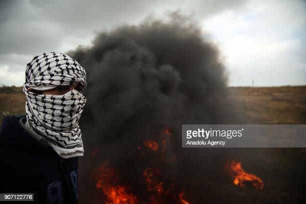 A facecovered protester stands near a burning tire set on fire in response to Israeli forces' intervention in a protest against US decision to...
