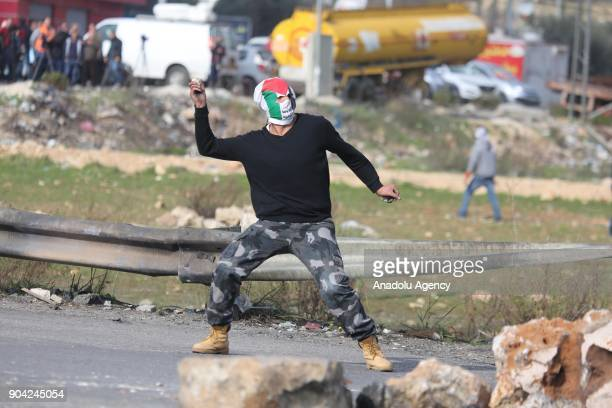 A facecovered protester throws a rock in response to Israeli security forces' intervention in a protest against US decision to recognize Jerusalem as...