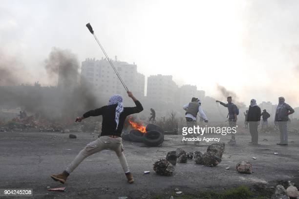 A facecovered protester throws a rock with a slingshot in response to Israeli security forces' intervention in a protest against US decision to...