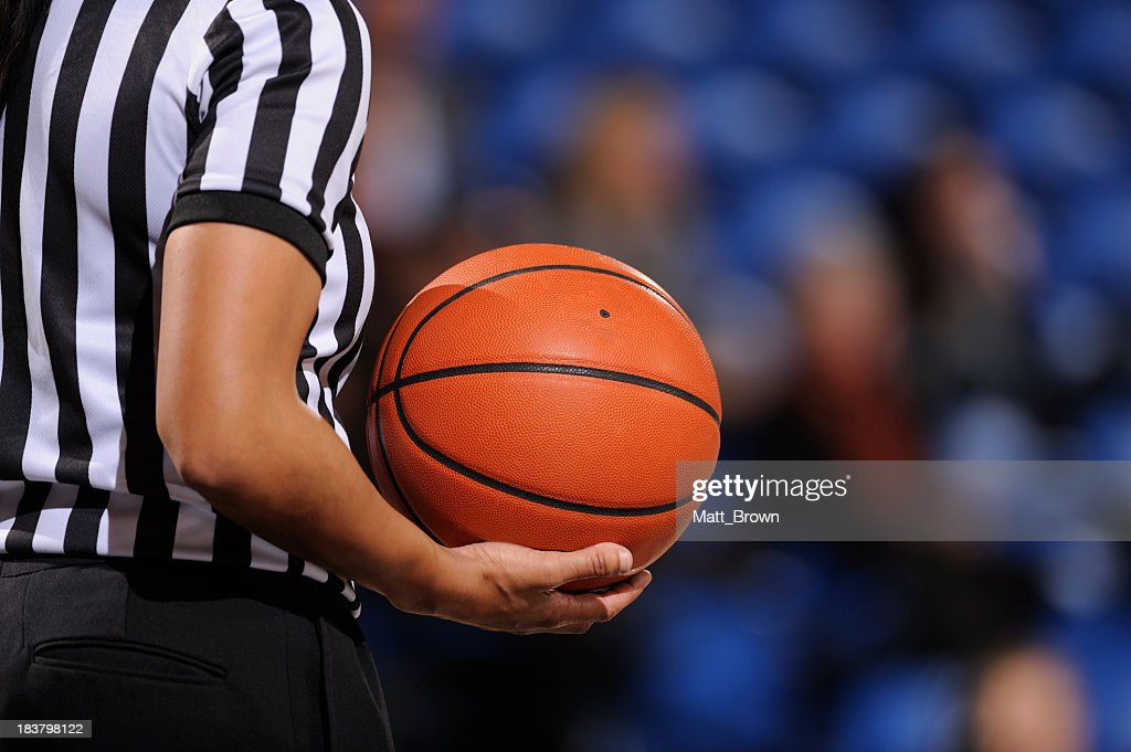 Faceless female basketball referee holds ball in one hand : Stock Photo