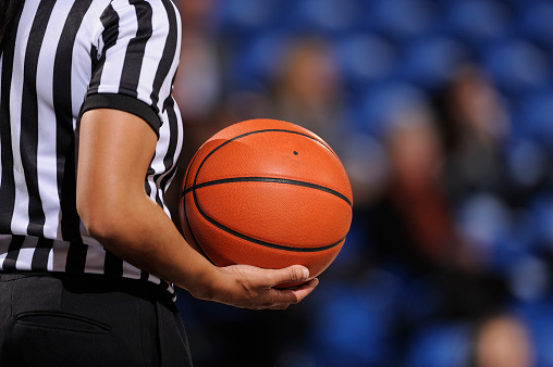 Faceless female basketball referee holds ball in one hand 183798122
