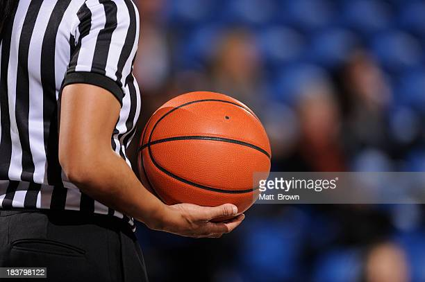 Faceless female basketball referee holds ball in one hand