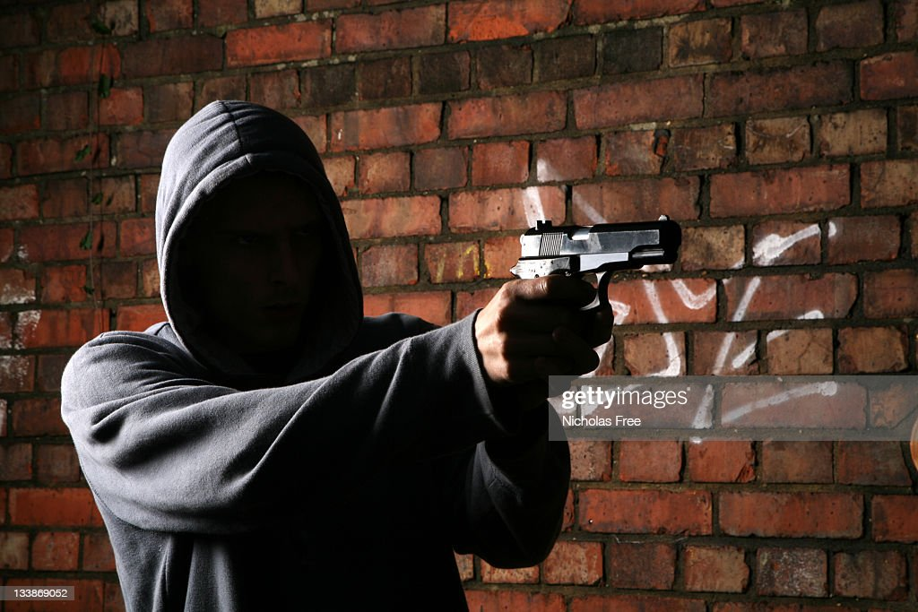 Faceless Gun Toting Hoodlum : Stock Photo
