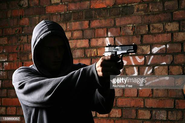 faceless gun toting hoodlum - shooting crime stock pictures, royalty-free photos & images