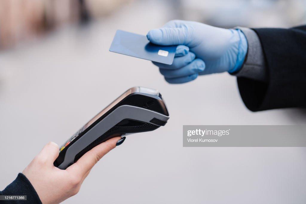 コロナウイルスの流行時に医療手袋を着用した顔のない人間は、プラスチックカードを保持し、安全のためにキャッシュレス支払いを試み、現代の技術を使用しています。パンデミック、ウ� : ストックフォト