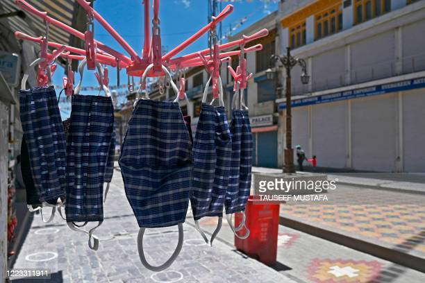 Facemasks hang outside a shop at a closed market amid concerns over the spread of the COVID-19 coronavirus in Leh, the joint capital of the union...