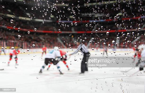 A faceoff between the Ottawa Senators and the San Jose Sharks is seen through drops of water on the plexiglass at Canadian Tire Centre on October 27...