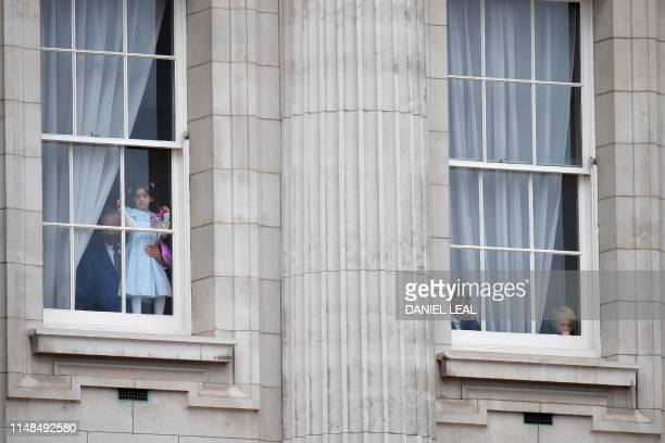 Faces at the windows of Buckingham Palace look out at crowds gathering ahead of the Queen's Birthday Parade 'Trooping the Colour' in London on June 8...