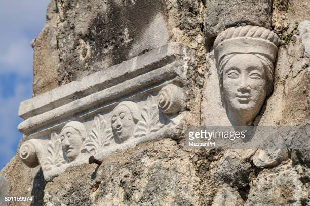 faces carved on the wall of a ruined church in venzone - byzantine stock pictures, royalty-free photos & images