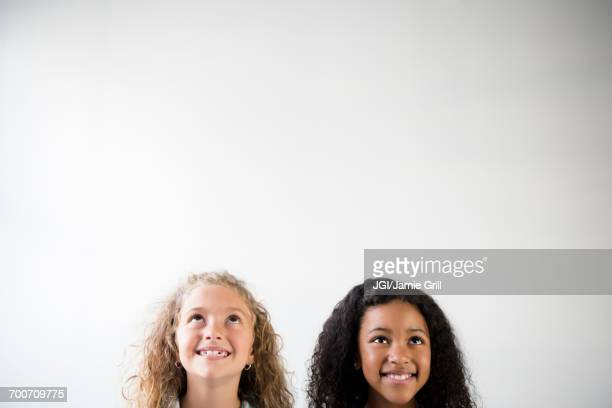 Faces of smiling girls looking up