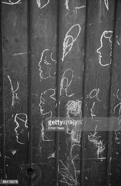 Faces scrawled on a fence in Mayfair London 1953