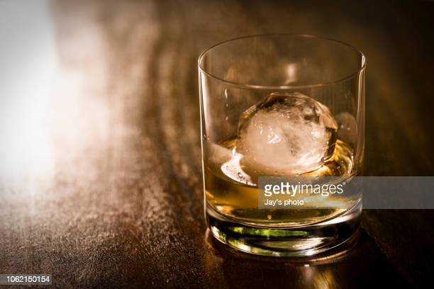 faceted glass of whiskey with ice - scotch whiskey stock pictures, royalty-free photos & images