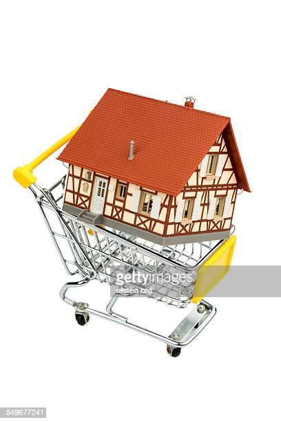 Fachwerkhaus im Einkaufswagen Symbolfoto für Hauskauf Finanzierung Kosten