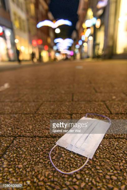 Facial mask on the ground in an almost deserted Diezestraat shopping street in the city center of Zwolle during the weekly shopping evening after the...