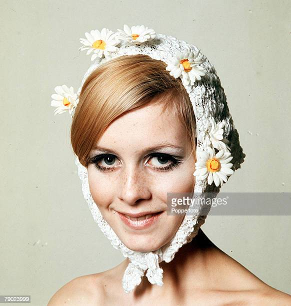 1966 A facial portrait of model Twiggy wearing a fashionable and quirky white bonnet hat which has daisies attached and also wraps round her chin...