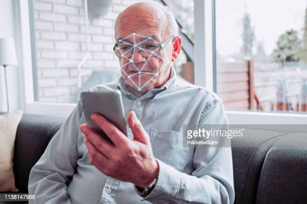 facial recognition software scans the face of senior man holding smart phone - biometrics stock pictures, royalty-free photos & images