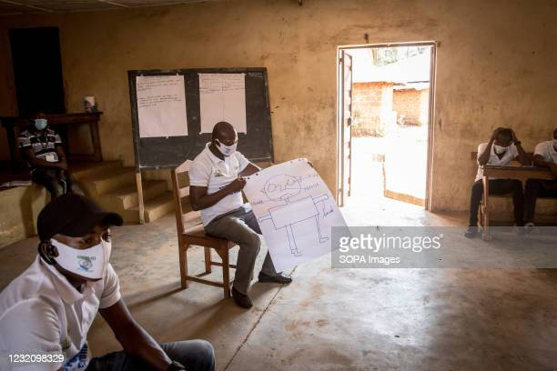 Facilitator holds a drawing of the body during a training led by the charity Goal aimed at helping Sierra Leone border communities prepare in case...