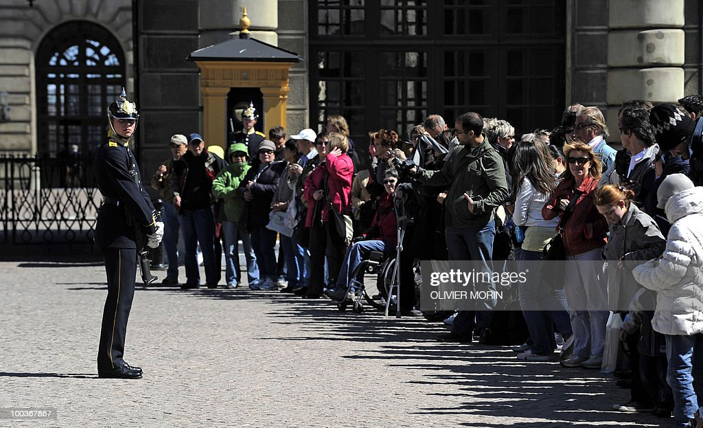 Facing a Royal Guard, tourists line up a as they wait for the changing of the guard in front of the Royal Castle in Stockholm on May 24, 2010. Many tourists paid a visit to the Swedish capital less than a month before Crown Princess Victoria 's wedding, the 32-year-old eldest daughter of King Carl XVI Gustaf.