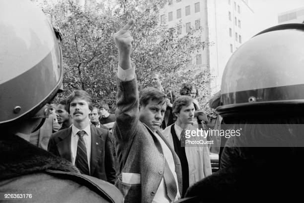 Facing police officers a protester holds up his middle finger during a demonstration about the Iran Hostage Crisis Washington DC November 9 1979...
