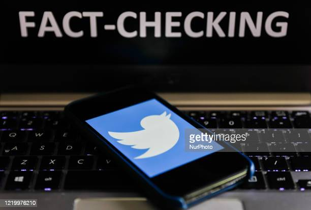 'Fact-checking' sign displayed on a laptop and Twitter logo displayed on a phone screen are seen in this illustration photo taken in Poland on June...