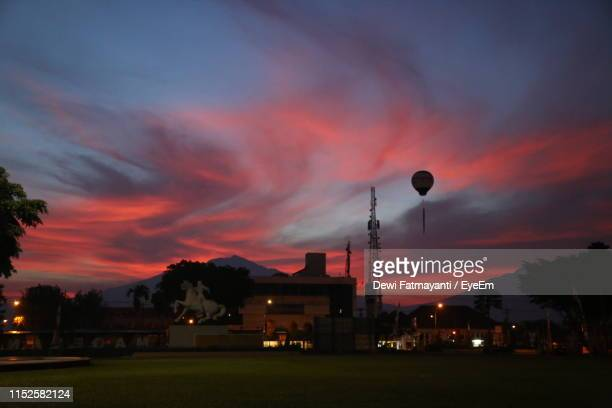 factory building against dramatic sky at sunset - dewi fatmayanti stock photos and pictures