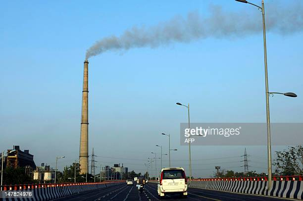 A factory chimney billows out smoke near a bridge on the Yamuna River in New Delhi on June 4 2011 Considered one of the holiest rivers in India the...