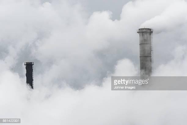 factory chimneys in smoke - luchtvervuiling stockfoto's en -beelden
