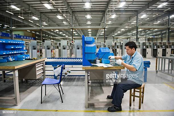 A factory employee sitting at his work station