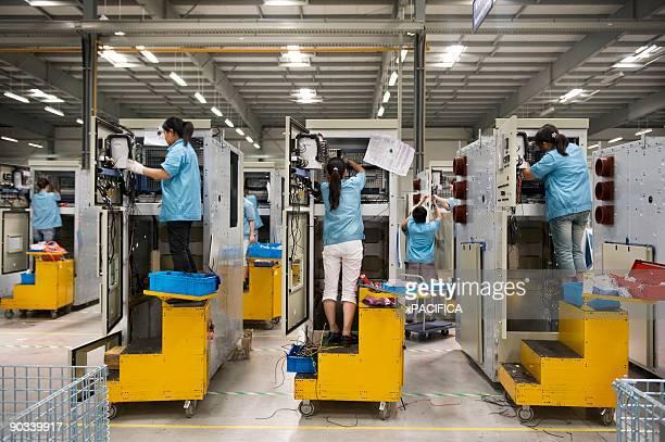 Factory employees wiring machinery.