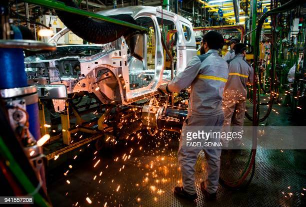 Factory employees work on a car assembly line at the RenaultNissan Tanger Car Assembly Plant in Melloussa east of the port city of Tangiers on March...
