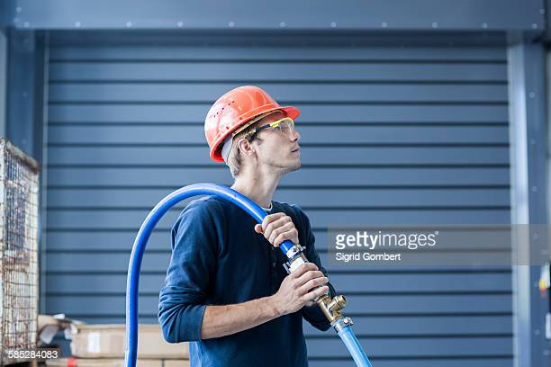 factory engineer carrying power cable over his shoulder - sigrid gombert stock pictures, royalty-free photos & images