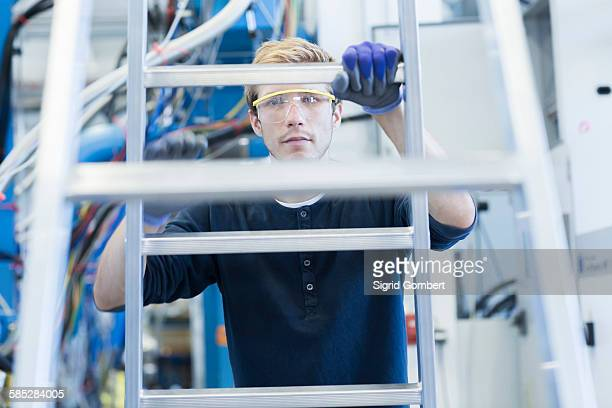 factory engineer climbing ladder in factory - sigrid gombert stock pictures, royalty-free photos & images