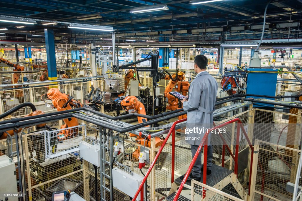 Factory engineer inspecting the work process : Stock Photo