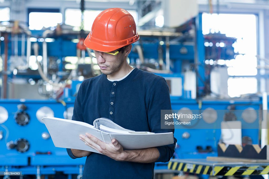 Factory engineer reading machinery instruction manual : Stock Photo