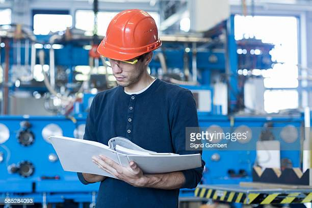 Factory engineer reading machinery instruction manual