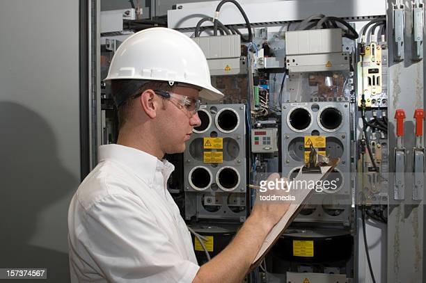 Factory engineer taking notes on clipboard