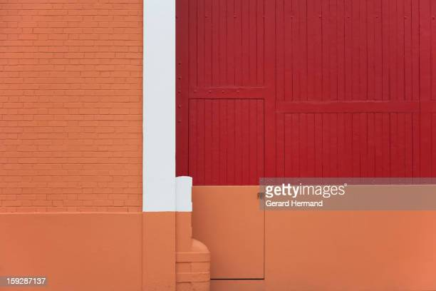 Factory entrance recently painted with art in red, beige and white. On the left: a brick wall. At the center of the photo: a little door included in...