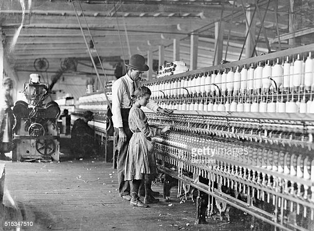 Factory interior with a young girl at a spinning machine instructed by a supervisor Photograph ca 1909