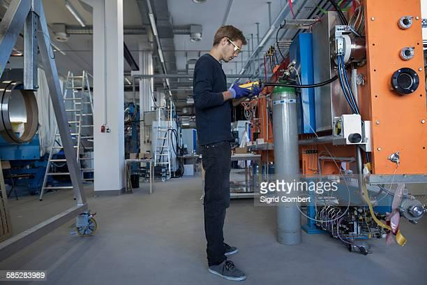 factory technician inspecting valves at control panel - sigrid gombert stock-fotos und bilder