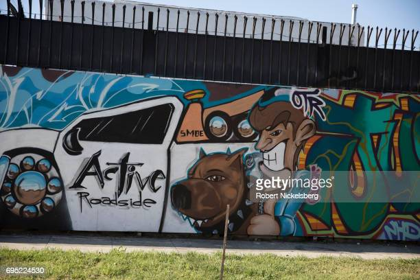 A factory wall with painted graffiti can be seen May 21 2017 in the Los Angeles Police Department's 77th Division neighborhood in Los Angeles...