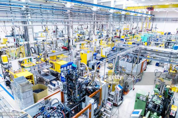 factory with automated machines and robots - electrical equipment stock photos and pictures