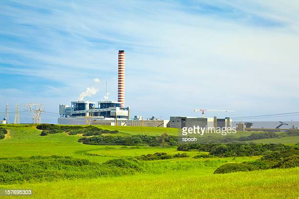 Fábrica con alto chimenea en un paisaje de verdes