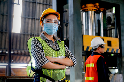 Factory woman worker or technician with hygienic mask stand with confident action with her co-worker  as background 1214565315
