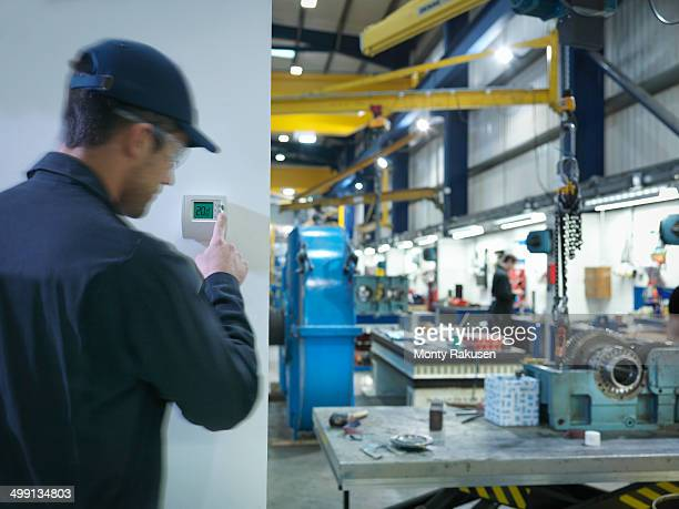 Factory worker adjusting thermostat in factory
