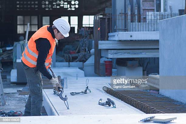 Factory worker attaching winch hook to concrete block in concrete reinforcement factory